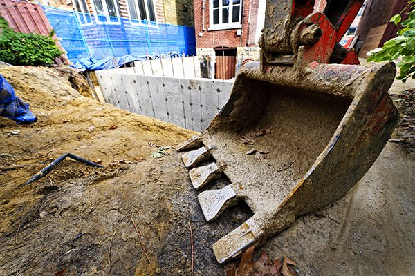 Backhoe scoop at residential home renovation construction site