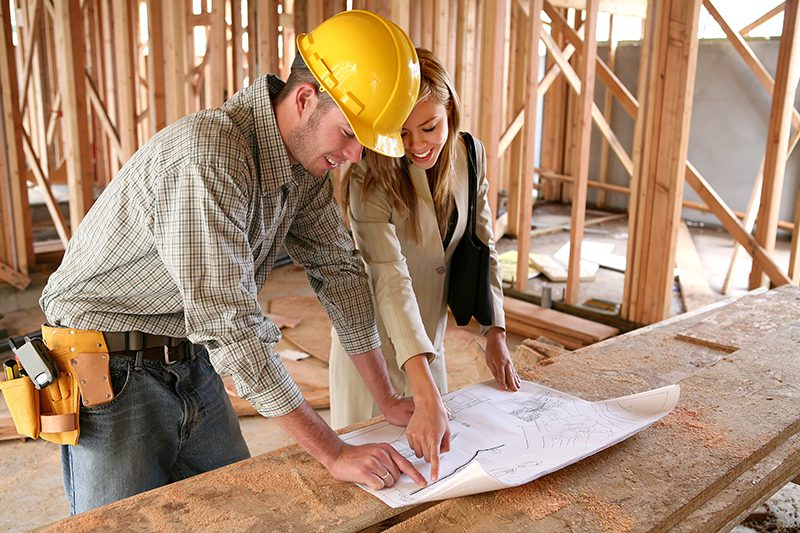A home designer working with a home buildering and inspecting the blueprints